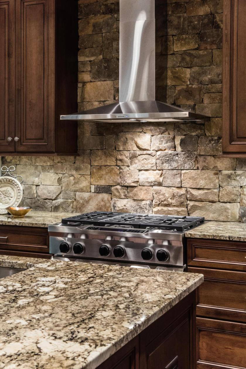 stacked-stone-backsplash-and-stainless-steel-range-hood